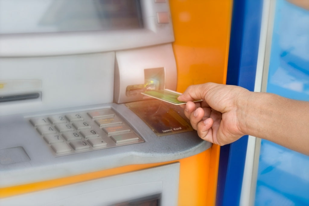 A person is inserting hand ATM card into bank machine to withdraw money
