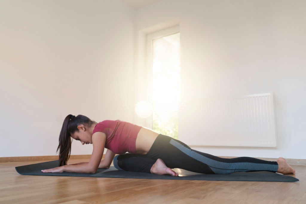 Young woman practicing yoga at home, sitting in a pigeon pose on an exercise mat.