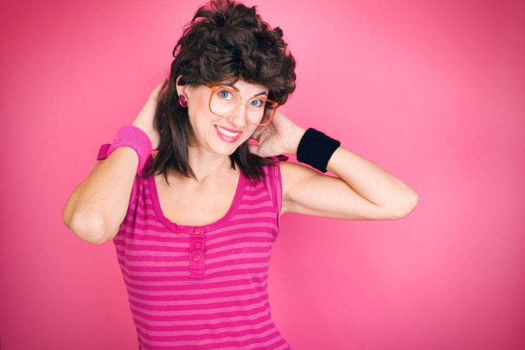 A humorous image of a woman dressed in 80's fashion including the popular mullet hairstyle.